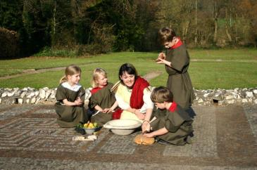 Lady dressed as Roman with children dressed as slaves on a mosaic at Rockbourne Roman Villa